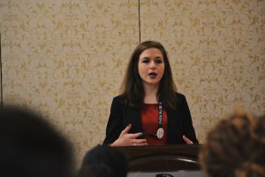 Photo of Kaitlyn (Katy) Brennan, wearing a black blazer and red shirt, speaking to a room.