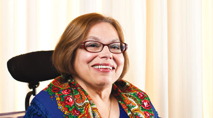 Photo of a white woman with shoulder-length auburn hair  in a wheelchair with colorful scarf and eyeglasses smiling.