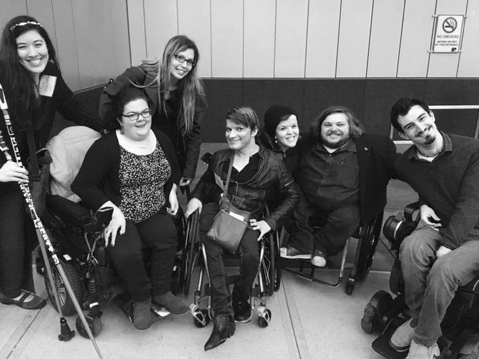 Picture of seven mentors with disabilities working in the media sector. The image is black and white and the mentors appear to be younger professionals, including four women and three men - four of which are wheelchair users and one of which is holding walking skies.. All of them are looking at the camera and smiling.