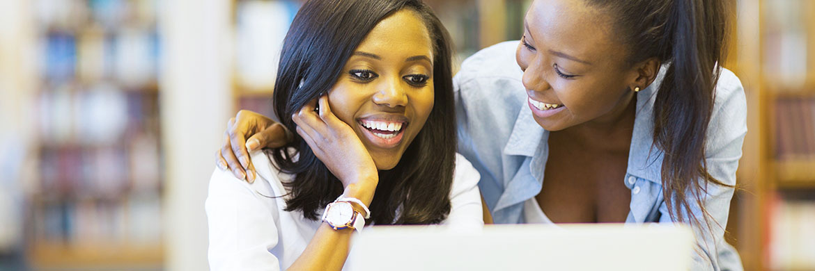 Two young women of color smiling, seated in the library at a computer.