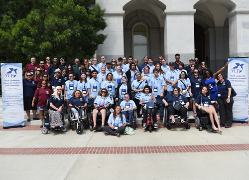 Group photo of youth and adults with disabilities outside, in front of the California State Capitol Building.
