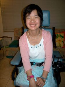 Young Asian woman in wheelchair smiling.
