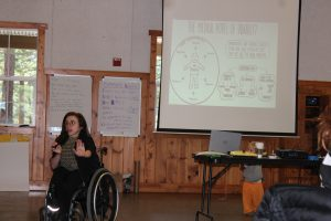 Youth in a wheelchair speaking into a microphone with a slideshow behind her.