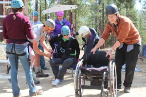 Grizzly Creek Ranch staffers help a youth in wheelchair get ready for the ropes course.