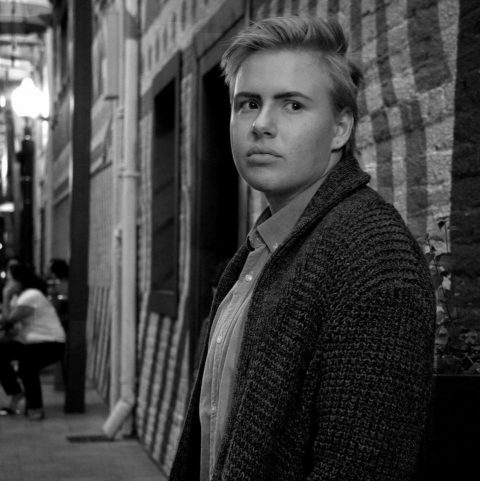 Black and white photo. Young, Caucasian male standing against a wall