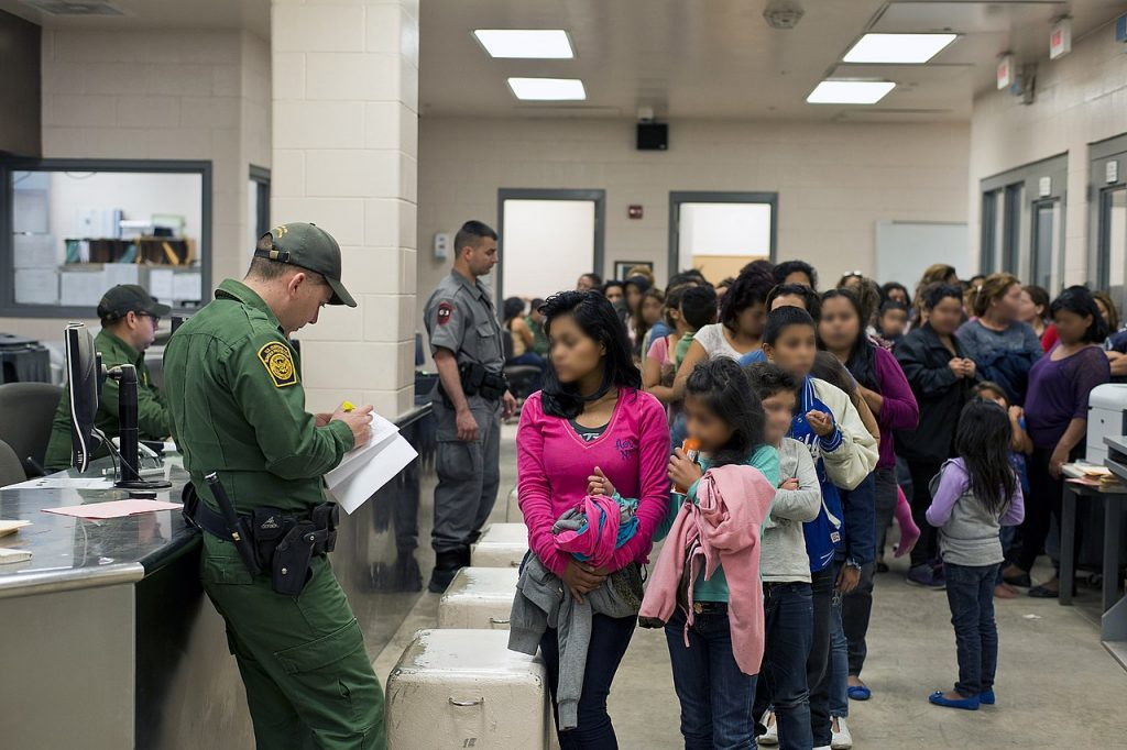Room full of brown-skinned youth without parents or guardians not smiling in line in a detention center. There are 3 white male guards.